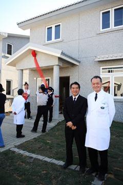 何日生與林俊龍,一同站在永久屋前與民眾歡慶入厝